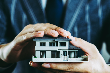 Businessman's hand holding a house model 스톡 콘텐츠