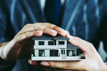 Businessman's hand holding a house model Standard-Bild