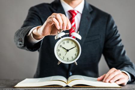 law suit: Businessman and alarm clock,studio shooting Stock Photo