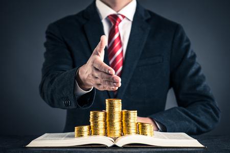 biznesmen i złota moneta umieszczona na książce