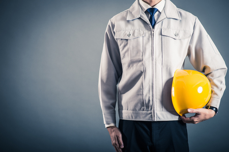 Men standing wearing work clothes with a gray background Standard-Bild