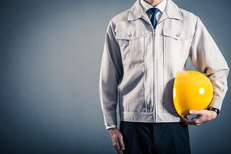 Mężczyzn stojących na sobie ubranie robocze na szarym tle Zdjęcie Seryjne