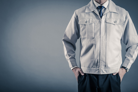 Men standing wearing work clothes with a gray background 스톡 콘텐츠