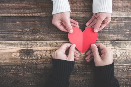 Le coppie maschii e femminili hanno un cuore rosso sul tavolo di legno Archivio Fotografico