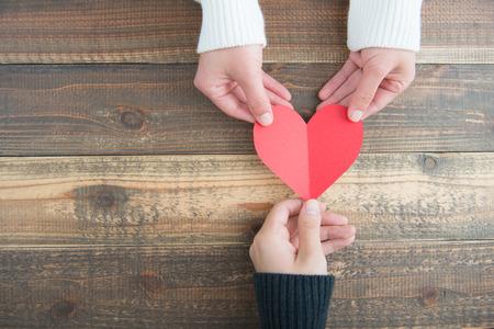 pareja de hombre y hembra tiene un corazón rojo en la mesa de madera Foto de archivo
