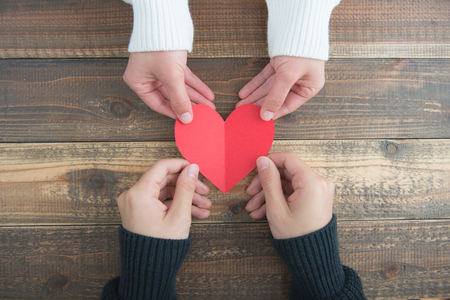 Male and female couple have a red heart on the wood table Stock Photo