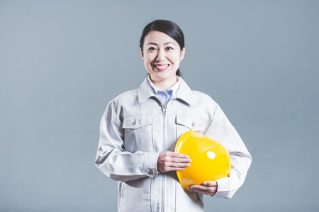 women standing wearing work clothes with a gray background