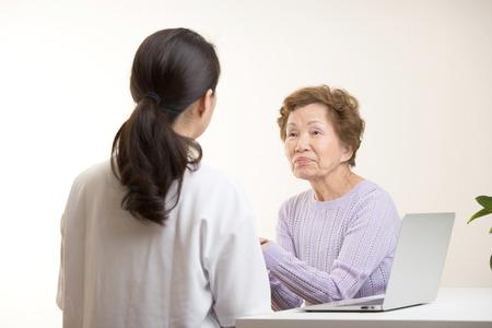 Asian elderly women talking to a doctor