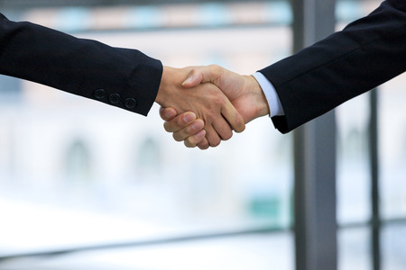 Shaking hands of businessmen and building background