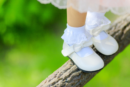 A small girl wearing shoes on a tree branch 版權商用圖片