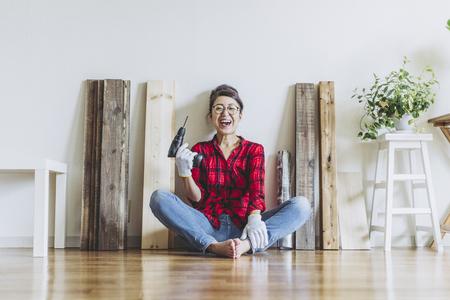 asiatische Frau, die mit diy Werkzeugen aufwirft