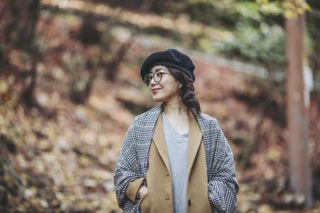 Asian woman with fallen leaves Reklamní fotografie