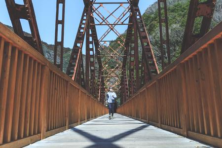 Asian lady running on the iron bridge 版權商用圖片