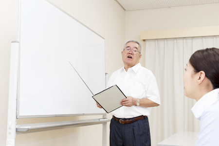 Elderly men teach by using white board