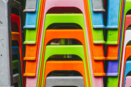 Lots of colorful chairs stacked