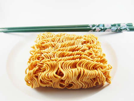 the instant noodles: Dried Instant Noodles and Green Chopsticks on White Dish