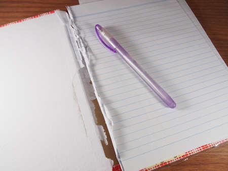 Opened and Torn Notebook with Ballpoint Blue Ink on Wood Background photo