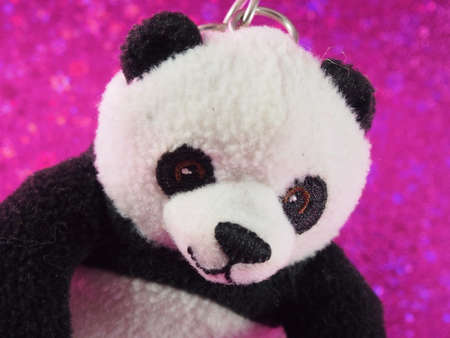 one panda: Panda Bear Doll with Showing Face on The Pink Bokeh Background Stock Photo
