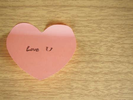 caes: Sensación de caída en amor con usted, escribiendo en la nota, forma de corazón en el fondo de madera
