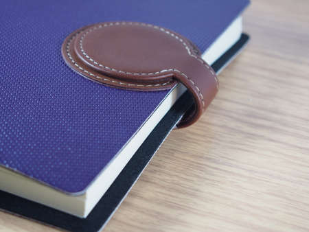 cerrando negocio: Notebook de negocios púrpura con la piel marrón para cerrar sobre fondo de madera