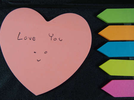 leatherette: Love you with smiling face, drawing and writing on pose its paper with colorful heart and arrow on black  leatherette background