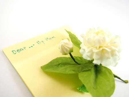 letter writing: Dear my mom on empty sticky note for being card with blurred handmade white jasmin flower, mothers day, Thai tradition, isolated on write background