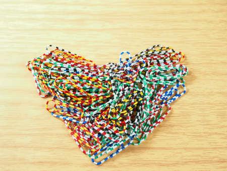 utiles escolares: Coloque los clips de papel de colores, la forma del coraz�n en el fondo de madera