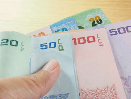 earn money: Pile of banknotes in hand, Thai baht money, earn and save money