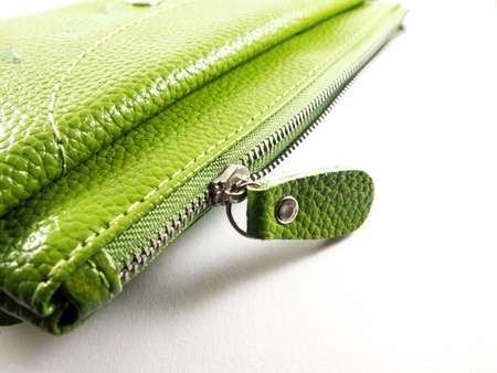 metal fastener: Handmade zipper on green leather purse, isolated on white background