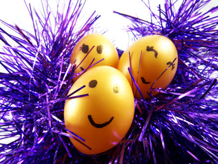 tuft: Plastic easter eggs with drawing happy smiling on faces, on violet tuft for easter festival