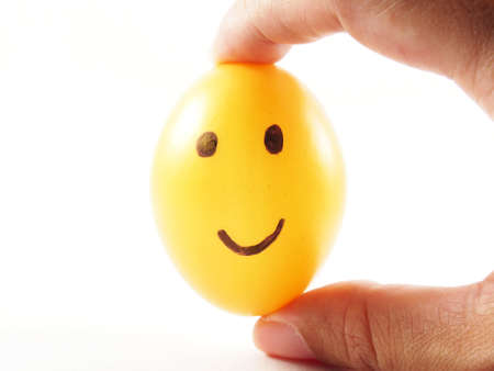 two finger: Plastic easter egg with drawing happy smiling on face, holding in two finger, for easter festival, isolated on white background Stock Photo