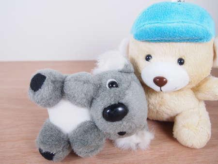 Pequeña muñeca gruesa de oso koala, tumbarse en el regazo del oso beige claro, piso de madera