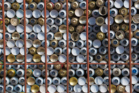 stapled: Dozens of stapled spray cans behind rusty bars Stock Photo