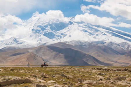 xinjiang: Lonely rider in mountain landscape in front of a cloudy blue sky