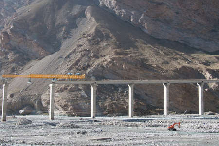 vast: Road construction in vast mountain area with single excavator in China Stock Photo