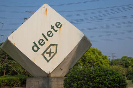 delete button: Giant rusty delete button in front of blue sky and electricity wires Stock Photo