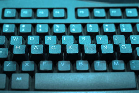 exploit: Keyboard with the keys hacking elevated in cyan light Stock Photo