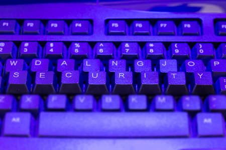 intrusion: Keyboard with the keys security elevated in blue light Stock Photo