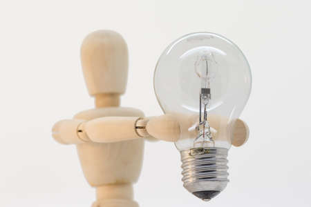 switched: Wooden guy presenting a light bulb that is switched off