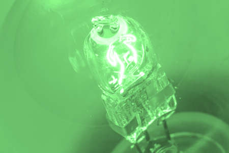 switched: Closeup of lightbulb with green background
