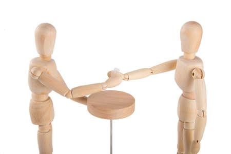 marioneta de madera: Wooden puppet couple having a drink on white background Foto de archivo