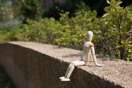 marioneta de madera: Marioneta de madera joven de relax bajo el sol en una pared