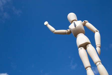 marioneta de madera: Wooden puppet waving in front of blue sky under the sunlight