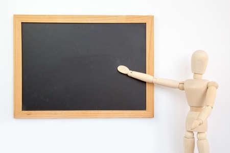 marioneta de madera: Wooden puppet businessman presents on blackboard