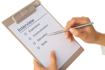 out of job: Womans hand fills out job interview checklist on white