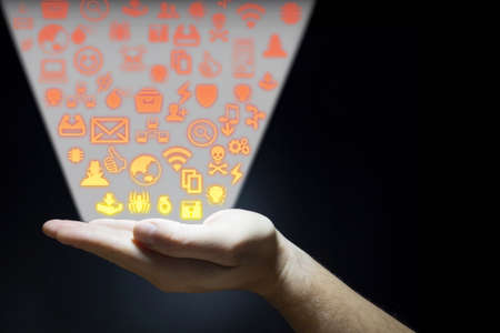 emitting: Hand emitting security threats icons in a ray of light on black