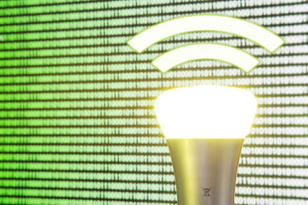 Lifi symbol with glowing bulb combined with wifi symbol in front of computer screen
