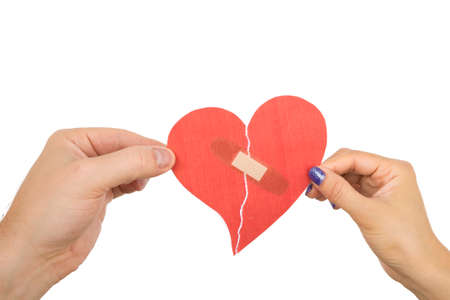 Male and female hand holding a red paper heart taped with bandages