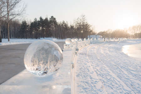 Row of ice balls at sunset in winter with reflection Stock Photo
