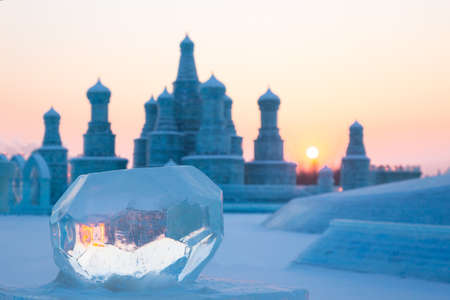 Ice balls at sunset in winter with orange reflection in front of blurry ice buildings Standard-Bild